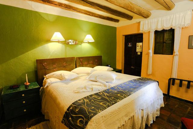 Rondreis Colombia Ricaurte Villa de Leyva Posada de San Antonio slaapkamer met dubbel bed