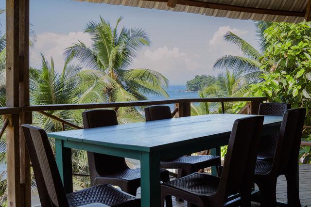 Rondreis Colombia Choco Nuqui El Cantil Ecolodge Tafel met tropisch behang op de achtergrond (maar dan echt)