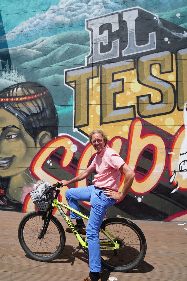 Rondreis Colombia Bogota fietstour poseren voor een graffiti kunstwerk