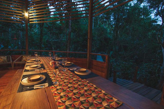 Rondreis Colombia Meta La Macarena La Manigua Lodge eten aan lange tafels in centrale gedeelte